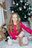 在Xmas树附近的愉快的小女孩 免版税库存照片