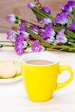 在yello杯子和黄油曲奇饼的一份热的咖啡在木头 库存照片