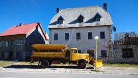 在Zabljak街道上的黄色除雪机在黑山 为在高地的冬天做准备 库存图片