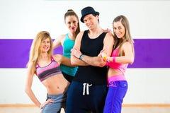 在zumba舞蹈学校供以人员摆在与妇女 库存照片