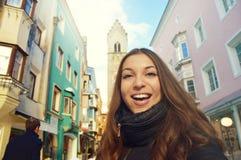 在Zwölferturm塔前面的愉快的微笑的女孩在老镇维皮泰诺,南蒂罗尔,意大利 库存照片