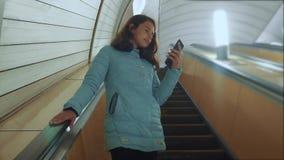 地下地铁在自动扶梯乘坐,拿着智能手机的生活方式的女孩少年 女孩深色的女儿 股票录像