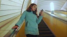 地下地铁生活方式的女孩少年在自动扶梯乘坐,拿着智能手机 女孩深色的女儿 影视素材