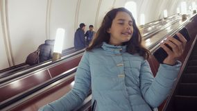 地下地铁的女孩少年在自动扶梯乘坐生活方式,拿着智能手机 女孩深色的女儿 影视素材