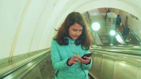 地下地铁的女孩少年在自动扶梯乘坐,拿着智能手机 女孩深色的女儿查寻 影视素材