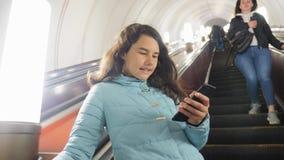 地下地铁的女孩少年在自动扶梯乘坐,拿着智能手机 女孩深色的生活方式女儿 影视素材