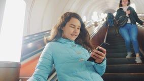地下地铁的女孩少年在自动扶梯乘坐,拿着智能手机 女孩生活方式深色的女儿 股票录像