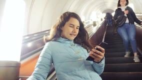 地下地铁的女孩少年在自动扶梯乘坐,拿着智能手机 小生活方式女孩深色的女儿 股票录像