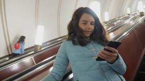 地下地铁的女孩少年在自动扶梯乘坐,拿着智能手机 生活方式女孩深色的女儿 影视素材