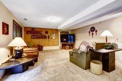 地下室有装饰的墙壁的家庭娱乐室 免版税库存图片