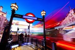 地下标志,在行动的红色公共汽车在皮卡迪利广场 伦敦,英国在晚上 图库摄影