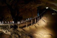地下洞游览 大小组桥梁的游人在黑暗中 新阿丰洞,阿布哈兹 免版税库存照片
