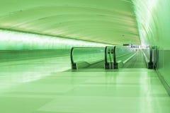 地下绿色有移动的走道的被点燃的隧道 图库摄影