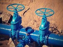 地下闸式阀,水在一条蓝色管道的管道阀门在重建以后 图库摄影