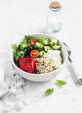 地中海奎奴亚藜碗用鲕梨,黄瓜,橄榄,烤了胡椒,希腊白软干酪,芝麻菜 在一个空白背景 库存照片