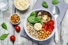 地中海奎奴亚藜hummus碗用茄子、蕃茄和sp 库存照片