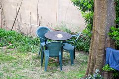 地中海庭院看法有家具的由一套三把塑料绿色椅子和一张桌 假日和享用 免版税库存照片