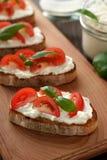 地中海开胃菜bruschetta用乳酪、蕃茄和蓬蒿在切板 库存图片