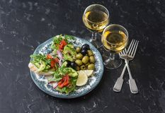 地中海样式开胃小菜和酒 熏制鲑鱼、鲕梨、芝麻菜bruschetta、橄榄和两杯白葡萄酒 库存照片