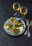 地中海样式开胃小菜和酒 熏制鲑鱼、鲕梨、芝麻菜bruschetta、橄榄和两杯白葡萄酒 免版税库存图片