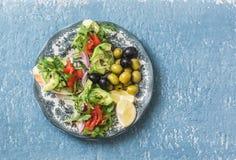 地中海样式开胃小菜 熏制鲑鱼,鲕梨,芝麻菜bruschetta,在蓝色背景的橄榄 免版税库存照片