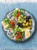 地中海样式开胃小菜 熏制鲑鱼,鲕梨,芝麻菜bruschetta,在蓝色背景的橄榄 库存图片