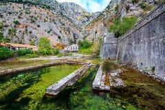 地中海横向 伸出的峭壁、老发电站在中世纪城市墙壁附近和河 库存图片