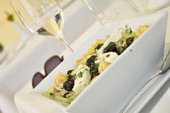 地中海沙拉的被掀动的看法用乳酪、油炸马铃薯片和oli 免版税库存图片