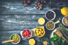 地中海烹调的概念 不同的果子、草本和开胃菜在蓝色木桌上 免版税库存图片