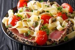 地中海烹调:与金枪鱼的意大利细面条面团在芝麻,机智 免版税图库摄影