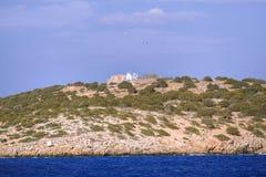 地中海的小希腊海岛,与缺乏植被和传统教会教堂的岩质小岛 库存照片