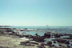 地中海的岩石岸有一艘船的在天际 库存照片