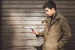 地中海种族浅黑肤色的男人年轻英俊的土耳其男性模型画象皮革外套的使用手电话  图库摄影