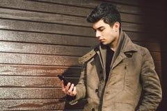 地中海种族浅黑肤色的男人年轻英俊的土耳其男性模型画象皮革外套的使用手电话  免版税库存照片