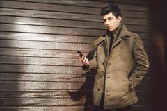 地中海种族浅黑肤色的男人年轻英俊的土耳其男性模型画象皮革外套的使用手电话  免版税图库摄影