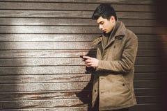 地中海种族浅黑肤色的男人年轻英俊的土耳其男性模型画象皮革外套的使用手电话  免版税库存图片