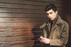 地中海种族浅黑肤色的男人年轻英俊的土耳其男性模型画象皮革外套的使用手电话  库存图片