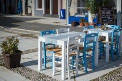 地中海餐馆的白色蓝色桌和椅子 库存照片