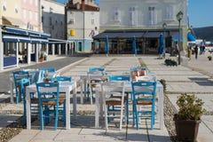 地中海餐馆的白色蓝色桌和椅子 免版税库存照片