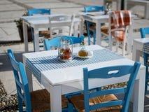 地中海餐馆的白色蓝色桌和椅子 库存图片