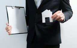 地产商、不动产房地产经纪商藏品片剂和房子的纸模型 得到通入回家 投资和购买物产 库存照片