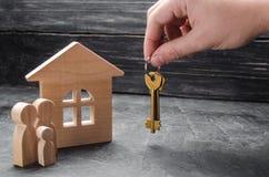 地产商` s手把握关键到房子 一个木房子和一个家庭有孩子 买卖的概念 库存照片