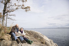 读地图的成熟夫妇在湖附近 库存图片