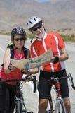 读地图的资深自行车骑士 免版税库存照片