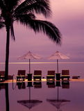 地平线在海洋、太阳懒人和阳伞的游泳池 免版税库存照片