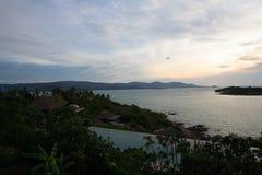 地平线在海洋的游泳池日落的,在庭院旁边 库存照片