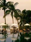 地平线游泳池,在庭院旁边的太阳懒人海洋的 库存图片