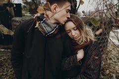 轻轻地拥抱在秋天公园的时髦的行家夫妇 Fashionabl 免版税库存图片