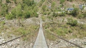地方人在尼泊尔运载在吊桥的一担子在河 影视素材