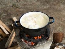 地方传统泰国厨房 使用烹调的火炉由在罐的煮沸在与橙色火焰和木柴的篝火 库存照片